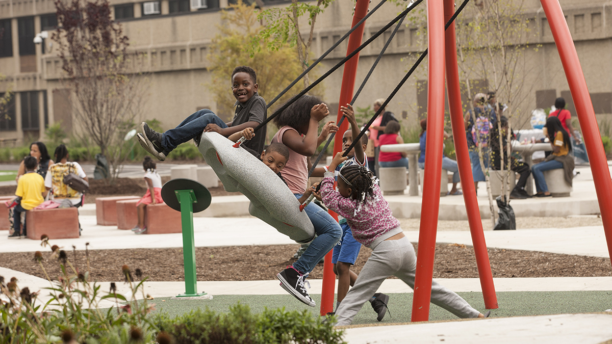 Children swing on a multi-person swing set at the John W. Cook Academy schoolyard, while adults sit in the background.